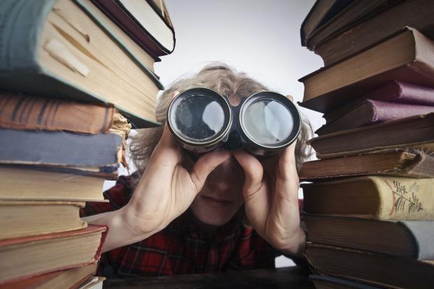 человек смотрит в бинокль, стопки книг