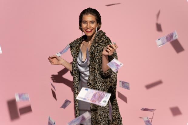 девушка в шелковом платье и искусственной шубе бросает деньги