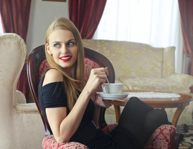 девушка в черном платье сидит в кресле