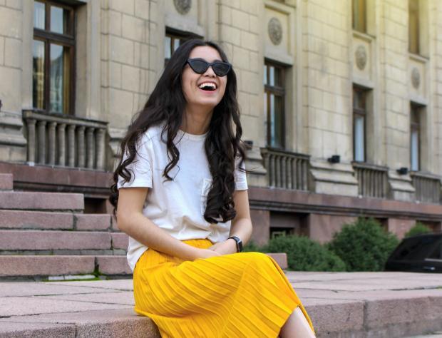 девушка в белой футболке и желтой юбке сидит на ступенях