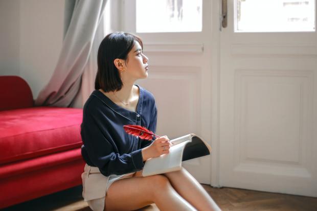 девушка задумчиво смотрит в окно, в руках тетрадь и ручка