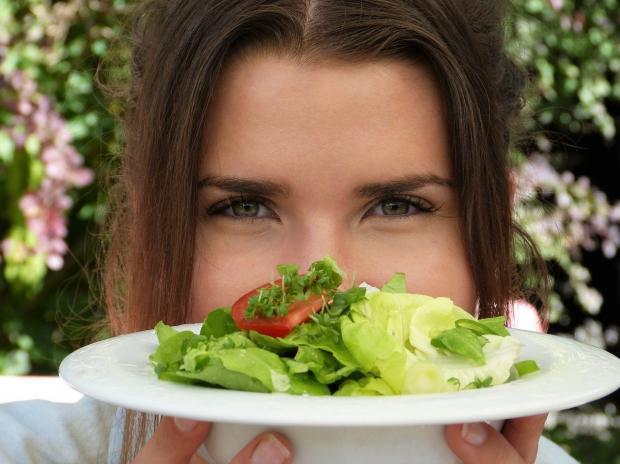 девушка держит белую тарелку с овощным салатом