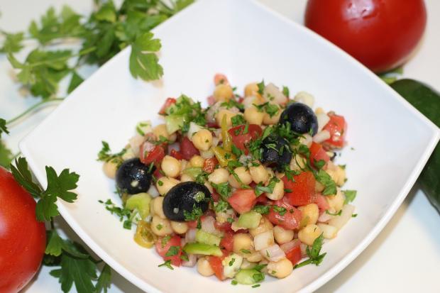 в белом блюде приготовлен салат из нута с овощами