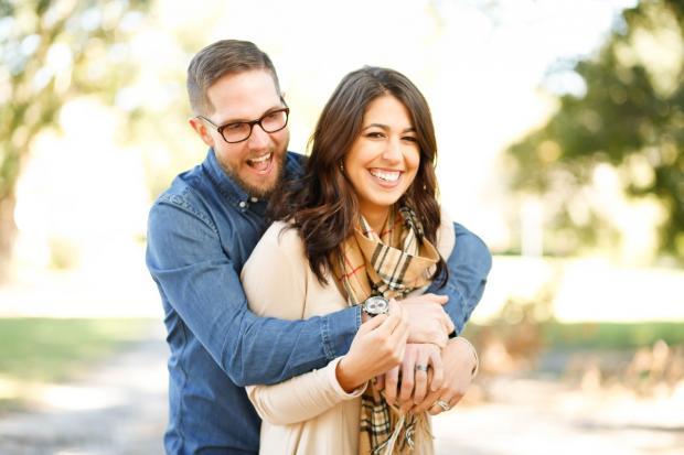 мужчина в очках обнимает смеющуюся девушку