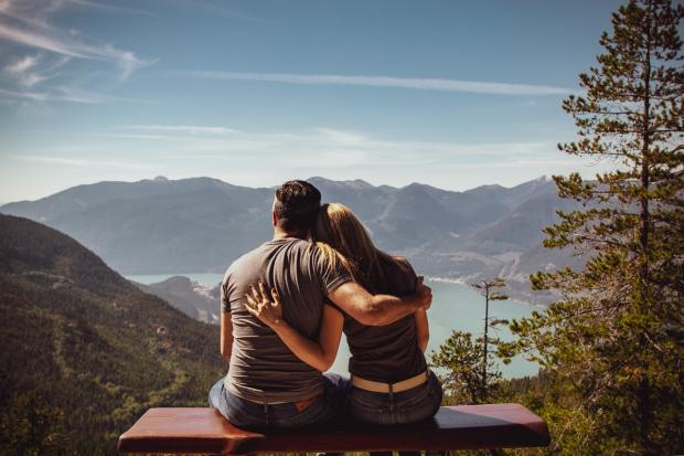 мужчина и девушка обнялись на вершине горы
