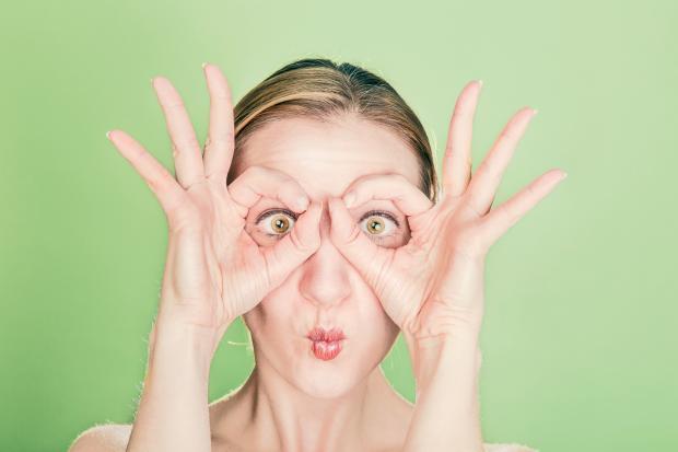 девушка держит пальцы вокруг глаз