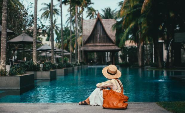 девушка в белой шляпе с коричневой сумкой сидит на берегу водоема