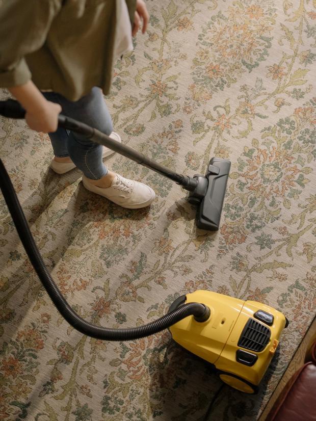 девушка чистит ковер желтым пылесосом