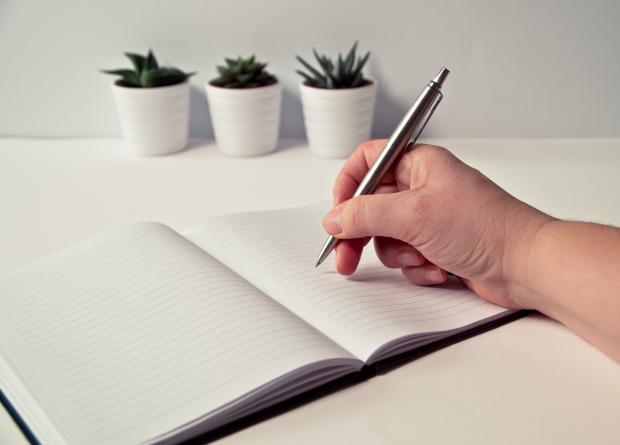 раскрытый блокнот, ручка в руке