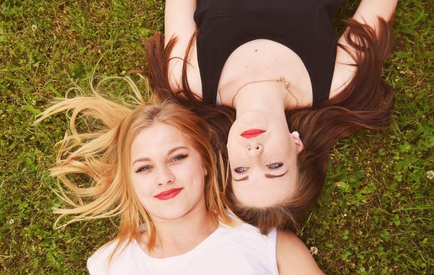 две девушка с длинными волосами лежат на зеленой траве
