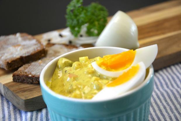 голубая тарелка с едой украшена разрезанными вареными яйцами