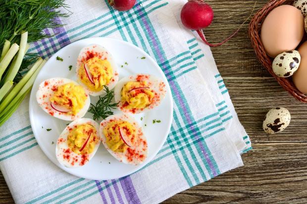 фаршированные яйца лежат на белой тарелке