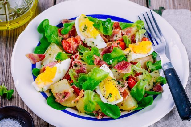 на столе стоит салат с вареными яйцами и картофелем