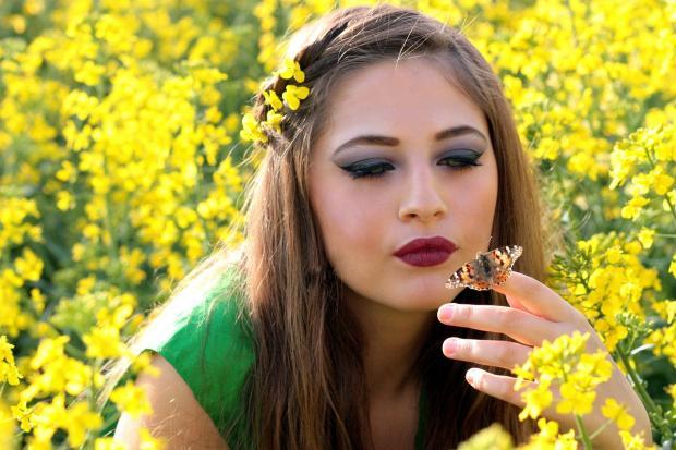 девушка среди желтых цветов держит на пальце бабочку