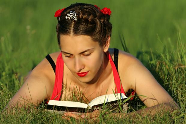 девушка лежа на траве читает книгу