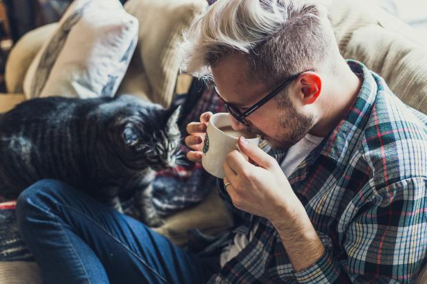 молодой человек пьет напиток из чашки