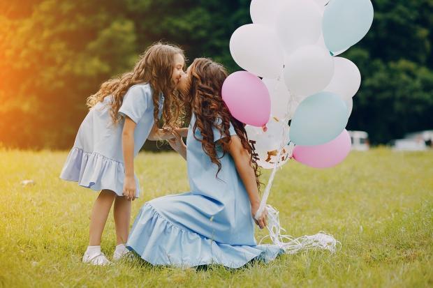 дочка целует маму на лугу с шариками