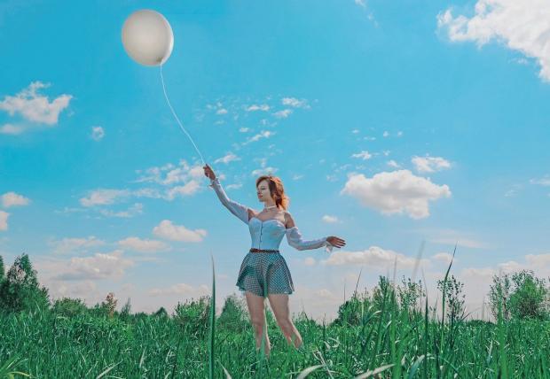 девушка в короткой юбке играет с воздушным шаром на фоне голубого неба