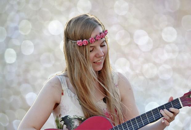 девушка с обручем на голове играет на красной гитаре
