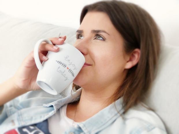 улыбающаяся девушка задумчиво пьет кофе из белой кружки