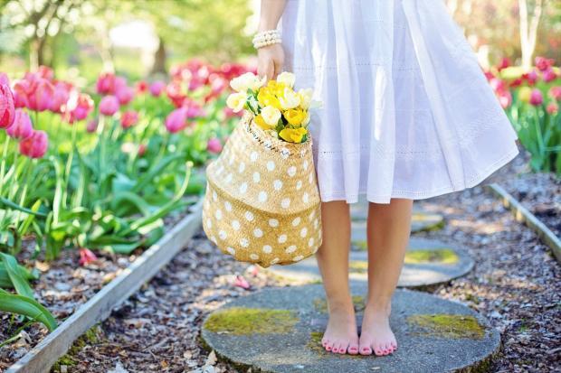 девушка с босыми ногами и в белом платье стоит в саду с корзинкой цветов в руках
