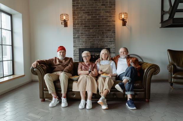 две пожилые пары сидят на диване