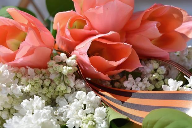 в букет из цветов вплетена Георгиевская ленточка