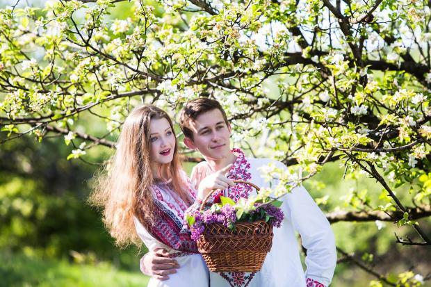 мужчина и девушка в национальных костюмах стоят у цветущего фруктового дерева