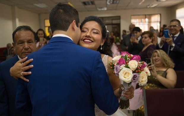 жених в синем костюме обнимает невесту с цветами