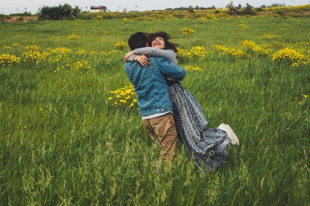 мужчина кружит девушку в цветущем поле