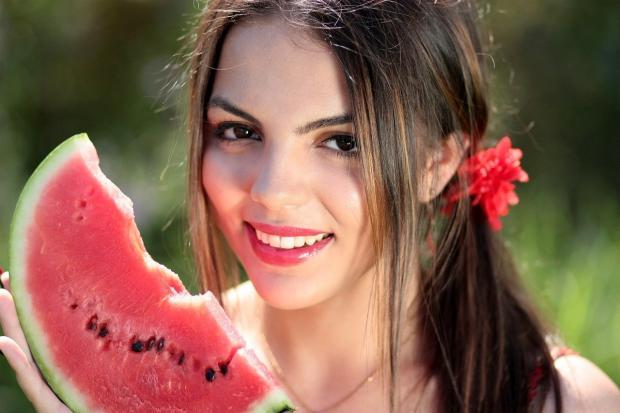 смеется девушка с красным бантом в волосах и долькой арбуза в руках