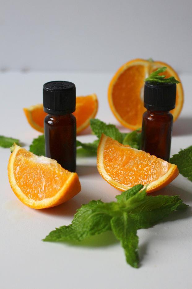 бутылочки с эфирным маслом стоят рядом с разрезанными апельсинами