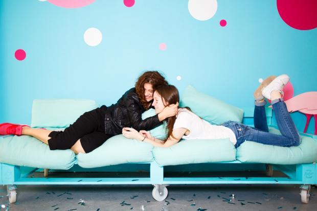 две девушки играют на диване
