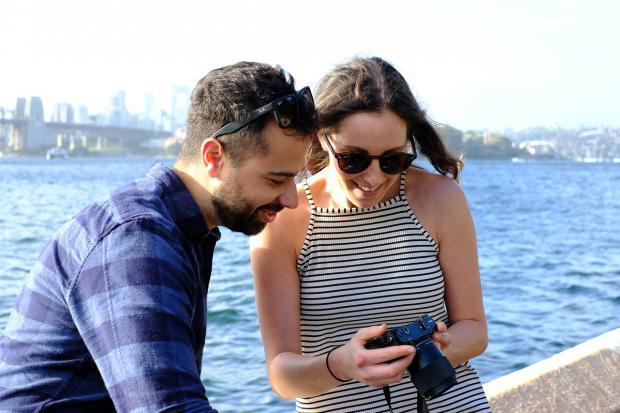 мужчина с девушкой на набережной смотрят на экран фотоаппарата