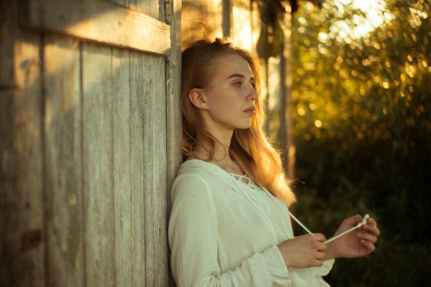 девушка в белой блузе возле деревянного забора
