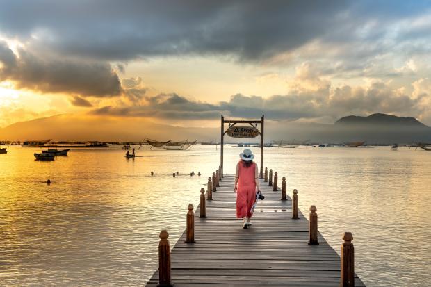 девушка в красном платье на мосту в море