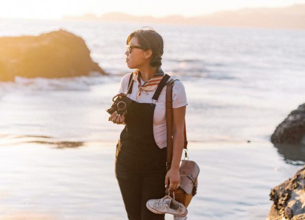 молодая девушка в черном комбинезоне стоит возле моря