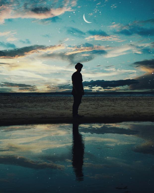 человек на морском побережье стоит ночью