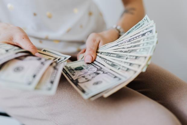 девушка в светлой одежде держит деньги в руках