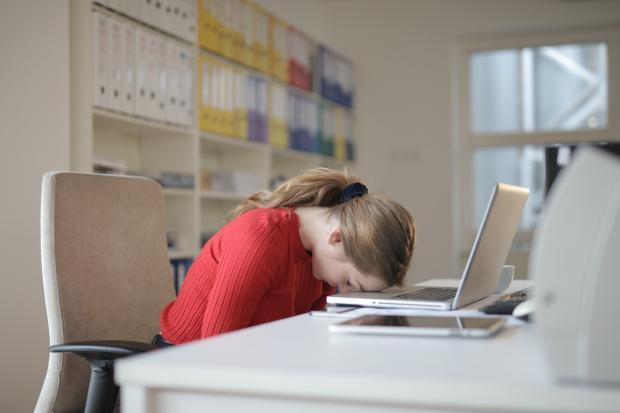 девушка спит сидя, уткнувшись головой в ноутбук