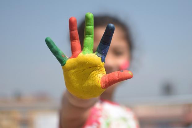 девочка растопырила окрашенную в разные цвета ладошку