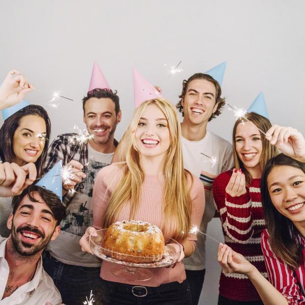 девушка держит в руках испеченный кекс на дружеской вечеринке