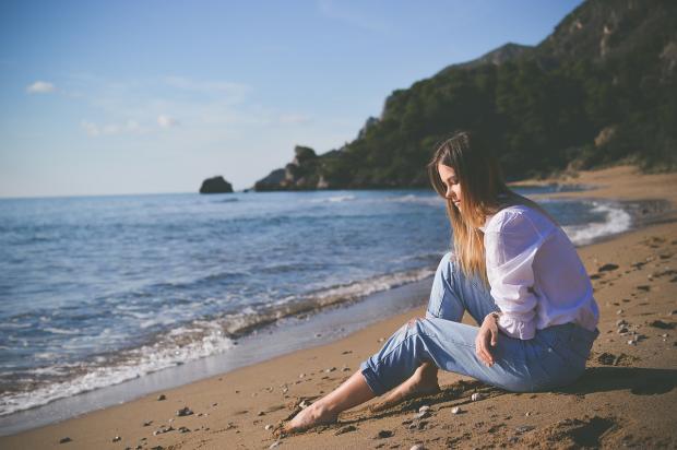 Длинноволосая девушка печально сидит на песчаном морском побережье