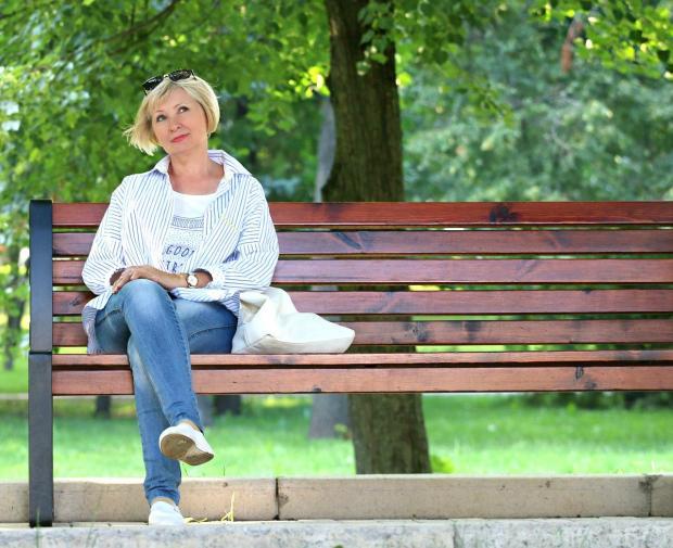 женщины в белом джемпере и джинсах сидит на деревянной скамейке