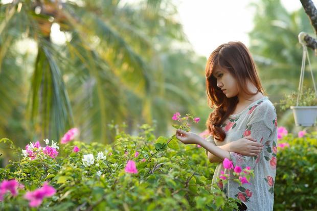 девушка рассматривает цветущие кустарники