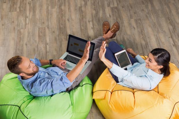 мужчина и девушка сидят в креслах с ноутбуком и планшетом