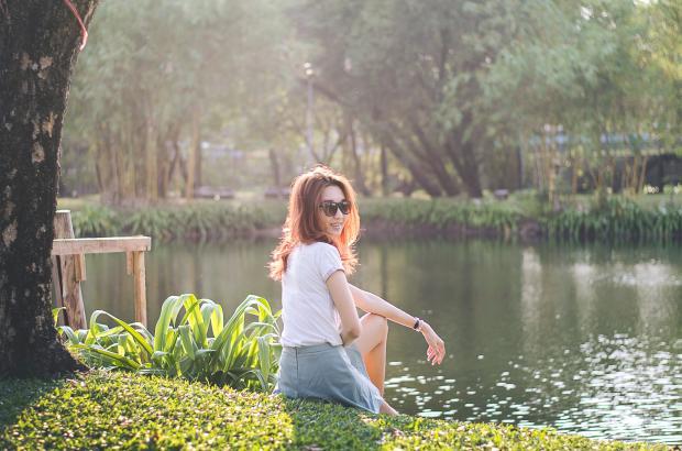 девушка в белой футболке и серой юбке возле водоема