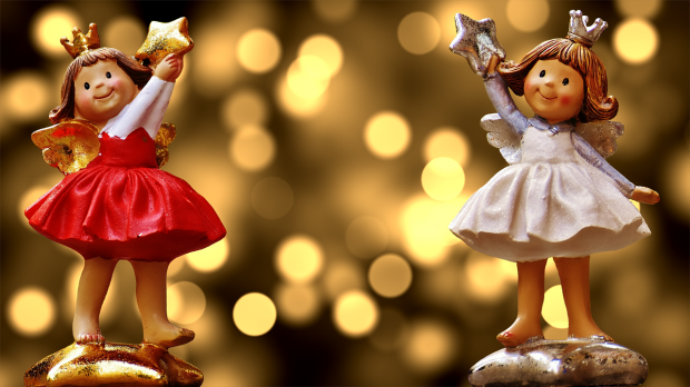 стоят две фигурки девочек-ангелов со звездочками в руках