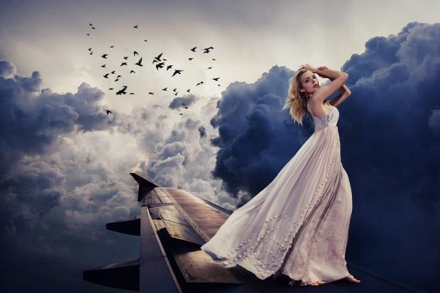 девушка в белом платье стоит под синим небом с летящими по нему птицами