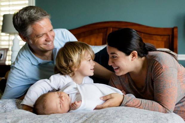 родители и старший ребенок смеются и склонились над новорожденным